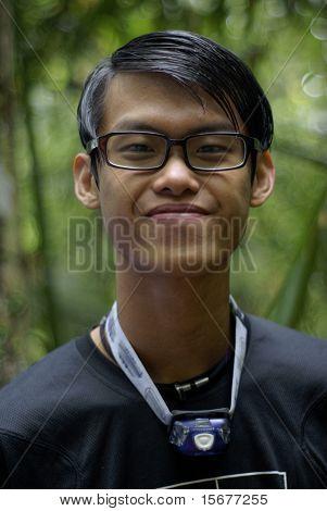 Slick asian man smiling outdoors