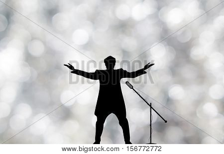 Silhouettes Of Showman Singer With Microphone On Blured Silver Shiny Background