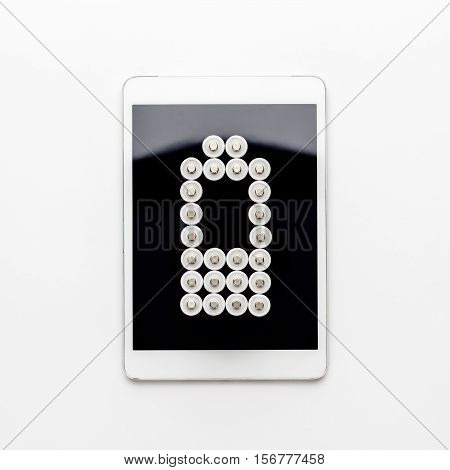conceptual image of battery charge level pictogram made of rechargeable batteries on top of the tablet computer over white background. not isolated