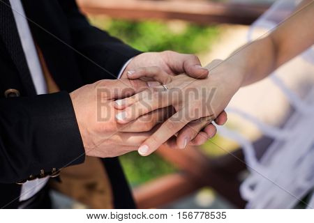 The groom wears the ring bride exchange rings wedding ceremony groom putting ring on bride's finger