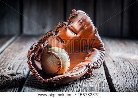 Baseball In A Leather Glove On Old Wooden Table