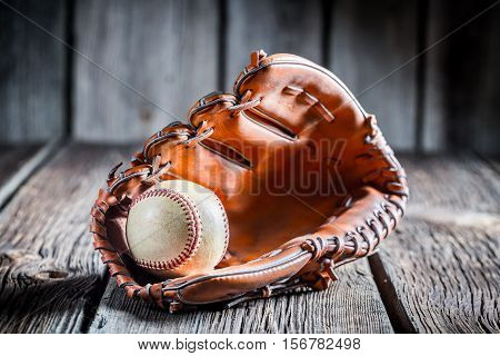 Age Baseball Glove And Ball On Old Wooden Table