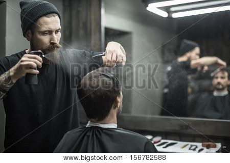 Attentive barber with a big beard splashes from the spray bottle at the hair of his client in the barbershop. He wears a black T-shirt with a black cap. They both reflected in a blurry mirror.