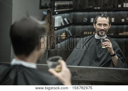 Happy bearded man looks into the mirror in the barbershop and holds a glass with a whiskey in the left hand. He has hairgrips on his head and a watch on the hand. Horizontal.