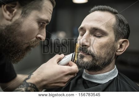 Talented bearded barber is trimming the beard of his client in a black cutting hair cape in the barbershop. He is using a cutting comb and a hair clipper. Customer sits with closed eyes. Closeup.
