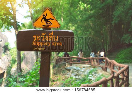 Sign showing a slippery area Thai and Chinese alphabet mean beware slippery. Obluang National Park Thailand.