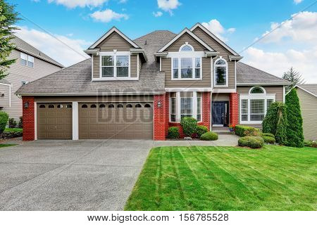 Beautiful curb appeal of beige house with red brick trim and nicely trimmed front garden. Northwest USA poster