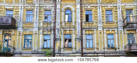Exterior of old deserted building with broken windows and balconies