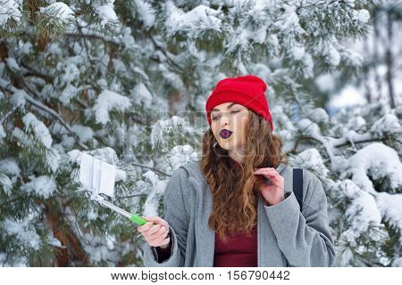 Portrait of pretty attractive girl hipster winter park. She makes selfie smartphone on sending a kiss. Youth street fashion. Winter fun. Walks in the open air.
