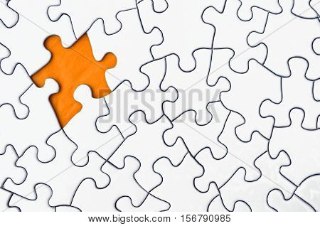 A top view image of a white jigsaw puzzle with a single piece missing,