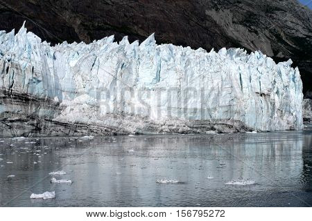 Margerie glacier and icebergs reflecting in clear ocean water in Glacier Bay National Park