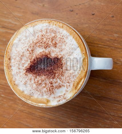 Cup of cappuccino coffee on wood background