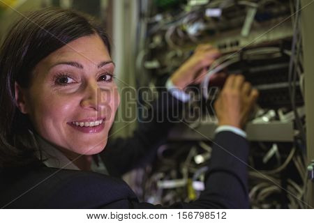 Portrait of technician checking cables in a rack mounted server in server room