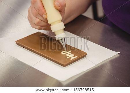 Worker writing happy birthday with piping bag on chocolate plaque in kitchen