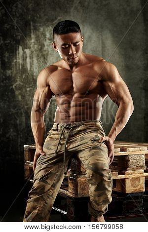 Muscular man sitting on pallet with bare upper body.