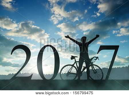 Cyclist with bicycle at sunset. Forward to the New Year 2017