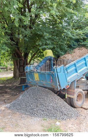 Dumper truck unloading soil or sand at construction site