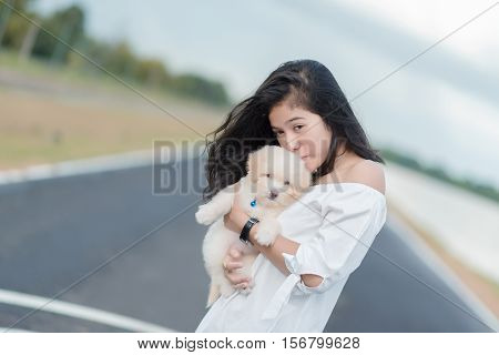 Asian woman beautiful young happy with long dark hair holding small dog.