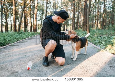 Young man with dog on rural road in forest. Sportsman playing with his puppy. Evening walk, happiness, joy concept