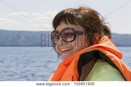 Cheerful woman in an orange lifejacket on a yacht at sea.