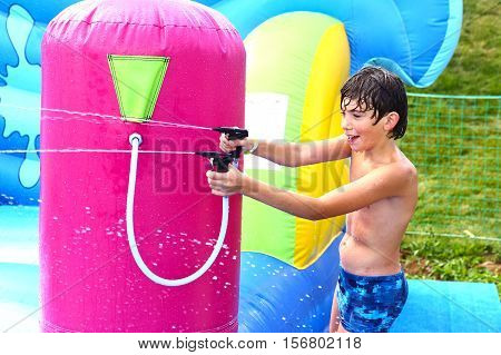 preteen boy in swimming slip in aquapark water spray shooting attraction trampoline close up laughing photo