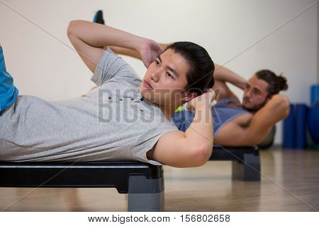 Two men doing aerobic exercise on stepper in fitness studio