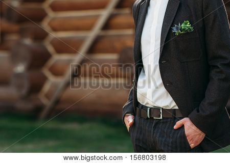 Unrecognizable groom standing outdoor, free space for text or advertisement. Man in black suit keep his hands in pockets. Nervous, waiting for bride, keeping calm fiancee