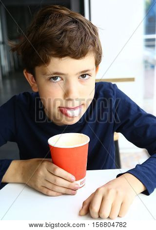 preteen boy with cappuccino coffee in paper glass show scum foam on tongue close up portrait in fast food restaurant cafe