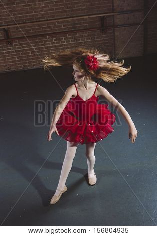 Active little dancer spinning and dancing at a dance studio