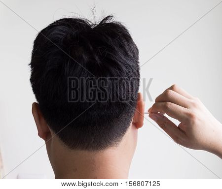 young man cleaning his ear with a cotton swab