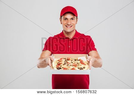 Young delivery man with pizza. isolated gray background