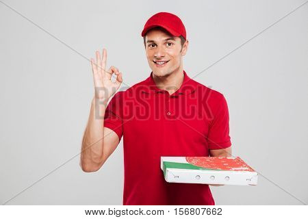 Front view of pizza delivery man. shows ok. looking at camera. isolated gray background