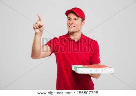 Pizza delivery man looking away. showing away. in studio. isolated gray background