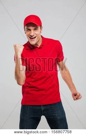 Photo of happy deliveryman. looking at camera. isolated gray background