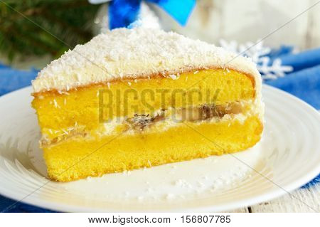 Gentle sponge cake with creamy banana layer sprinkle coconut on top. Option festive dessert for Christmas New Year. Close-up