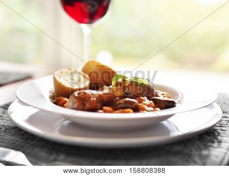 Coq au Vin, french chicken meal or dinner with selective focus and red wine.