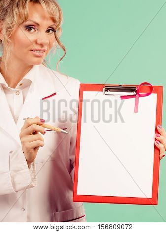 Diagnosis concept. Middle aged female doctor with pen showing red empty folder with pink breast cancer awareness ribbon