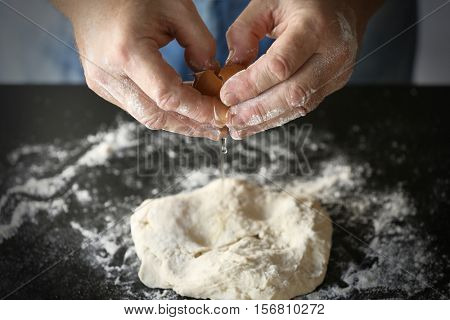 Male hands adding fresh egg to dough on table