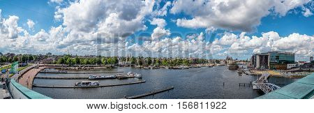 Amsterdam Netherlands - August 1 2016: Panorama of Amsterdan a blue sky day with pretty white clouds from Nemo Science Museum