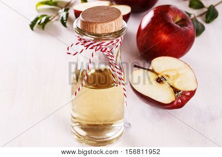 Apple cider vinegar and red apples over white wooden background. Selective focus