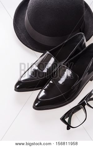 Fashion items with pair of black shoes hat and eye glasses
