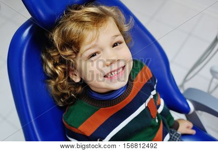 small child with curly hair in a striped sweater, sitting in the dental chair. Examination of the teeth at the dentist.