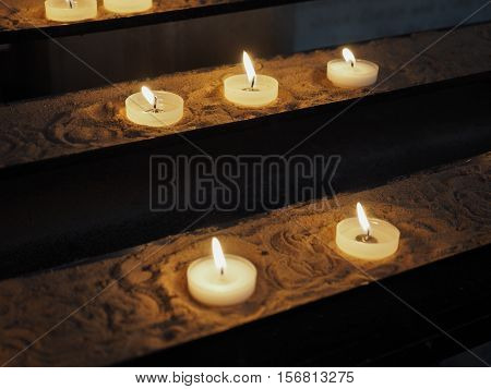 Candles lit by worshippers in a Christian church
