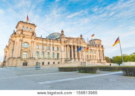 German Reichstag the German parliament building in Berlin at sunset. Some german flags and one European waving. Politics and architecture concepts.
