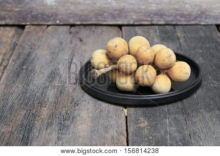 southern langsat Wollongong on a black plate in wooden background tropical fruit at South of Thailand