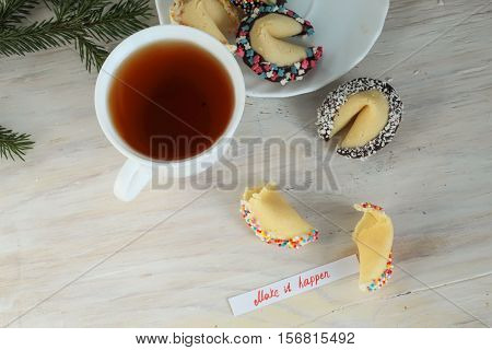 open Fortune cookie decorated with chocolate make it happen and a cup of tea
