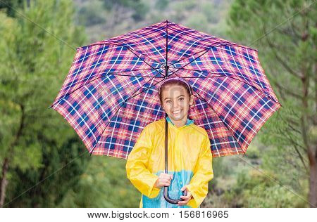 Happy little girl with colorful umbrella and raincoat playing in the rain