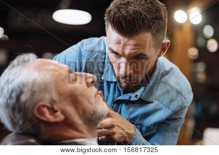 Pedantic work. Concentrated handsome bearded hairstylist standing and cutting beard of nice senior man sitting at barbershop.
