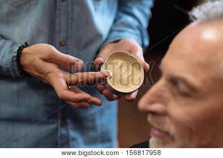 Last steps. Close up of male hairstylist holding jar with hair gel before putting it on senior client at barbershop.