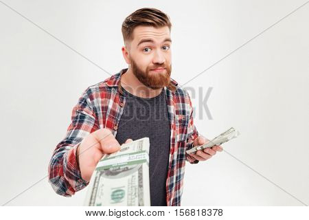 Portrait of a happy casual man giving money at camera over white background